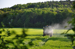 Tractor Spraying Pesticide. In the field royalty free stock images