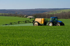 Tractor spraying pesticide in a field of wheat stock photo