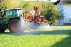 Tractor spraying pesticide near houses. A Tractor spraying pesticide near houses stock images