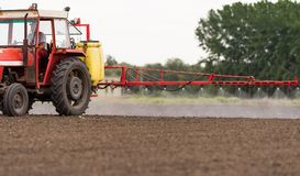 Tractor spraying pesticides on arable field with sprayer stock image