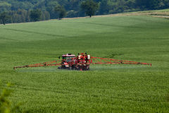 Tractor spraying pesticides on big green field Royalty Free Stock Images