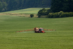 Tractor spraying pesticides on big green field Royalty Free Stock Image