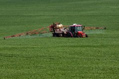 Tractor spraying pesticides. On big green field with young grain Royalty Free Stock Photography