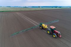 Tractor spraying the pesticides on the field Stock Photo