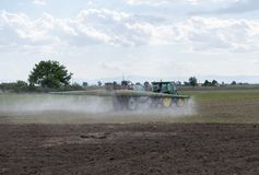 Tractor spraying pesticides on field with sprayer. Farmer fertilizes plants. stock photos