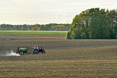 Tractor spraying pesticides, on fields in the spring, landscape Stock Images