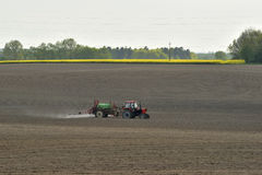 Tractor spraying pesticides, on fields in the spring Royalty Free Stock Images
