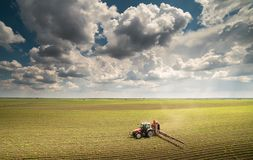 Tractor spraying pesticides on soybean field with sprayer at spr Stock Image