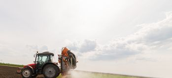 Tractor spraying pesticides on wheat field with sprayer at sprin stock photos