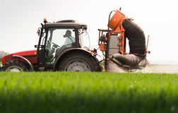 Tractor spraying pesticides on wheat field with sprayer at sprin stock photography