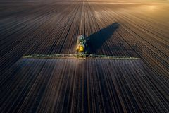 Tractor spraying soil in field. Aerial image of tractor spraying soil and young crop in springtime in field royalty free stock image