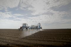 Tractor spraying soil in field stock image