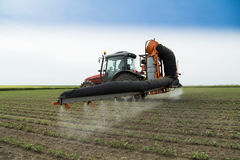 Tractor spraying soy bean field protecting it from pests Royalty Free Stock Photography
