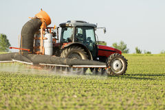 Tractor spraying soybean crops field. With sprayer, pesticides and herbicides Stock Images
