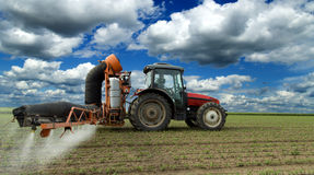Tractor spraying soybean crops field. With sprayer, pesticides and herbicides Royalty Free Stock Images