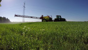 Tractor spraying wheat field with herbicide insecticide pesticide in spring