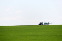 Tractor spraying wheat field with sprayer in springtime. Herbicides and pesticides stock photos