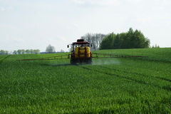 Tractor spraying wheat v3. Tractor spraying wheat field in spring Royalty Free Stock Photos