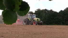 Tractor spread fertilizer sow field. Tree leaves move. BIRZAI, LITHUANIA - AUGUST 22, 2014: Tractor spread fertilize sow agriculture field on August 22, 2014 in stock video