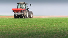 Tractor spreading artificial fertilizers Stock Images
