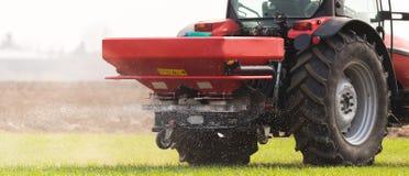 Tractor spreading artificial fertilizers Stock Photos