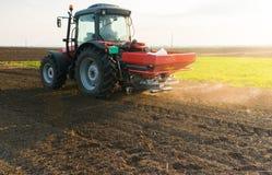 Tractor spreading artificial fertilizers. In field Stock Photo