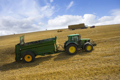 Tractor spreading fertilizer in sunny rural field Stock Image