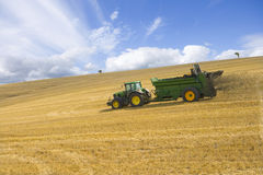 Tractor spreading fertilizer in sunny rural field Stock Images