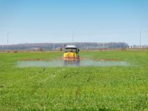 Tractor spreading herbicides over a green field Royalty Free Stock Photos