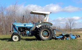 Tractor in Spring field with German Shepherd Dog p. A old blue and white tractor in an early spring field featuring blue skies with puffy clouds. A German royalty free stock photography