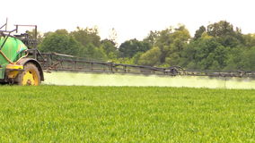 Tractor sprinkler spray field plants with chemical herbicide stock video