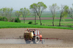 Tractor sprinkling pesticides againt bugs on plowed land on sunn. Y spring day Royalty Free Stock Photography