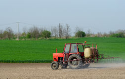 Tractor sprinkling pesticides againt bugs. On plowed land on sunny spring day Royalty Free Stock Image