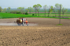 Tractor sprinkling pesticides againt bugs. On plowed land on sunny spring day Stock Image