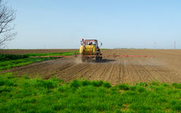 Tractor sprinkling pesticides againt pests. Tractor sprinkling pesticides againt bugs on plowed land on sunny spring day Royalty Free Stock Image
