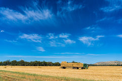 Tractor stacking hay bales on trailer Stock Photos
