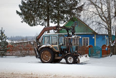 The tractor standing near a lodge in the village. Rural life Stock Photo
