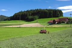 Tractor standing next to mowed grass. Swiss farm stock photos