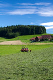 Tractor standing next to mowed grass. Swiss farm Stock Photos