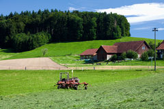 Tractor standing next to mowed grass. Swiss farm royalty free stock photos