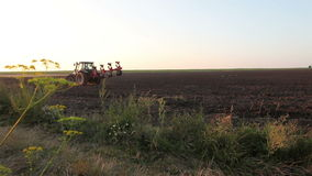 Tractor stands in a field of black earth at sunset Royalty Free Stock Images
