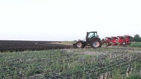 Tractor stands in a field of black earth at sunset Royalty Free Stock Photos