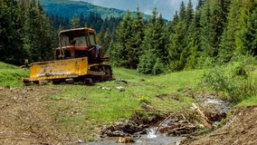 The tractor stands in the mountains near the stream. Beautiful summer day in the mountains. Daily timelapse. Pine forest. Old tractor. Mountain Creek. Bright stock video