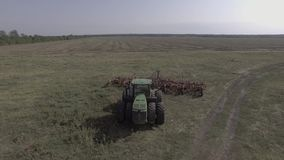 The tractor stands still in the middle of the grass field, the quadcopter flies up and takes the tractor from above CLog, 4 K. The tractor stands still in the stock footage