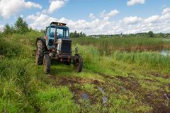 Agricultural machinery rests. The tractor stands in the tall grass on the shore of the pond Stock Photo