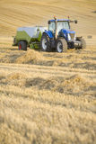 Tractor and straw baler in rural field stock image