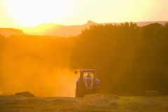 Tractor straw baling in sunny, rural field Royalty Free Stock Photography