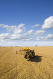 Tractor straw baling in sunny, rural field Stock Photos