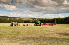 Tractor at Straw harvesting. Tractor and roller straw wagon Stock Photos