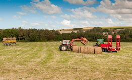 Tractor at Straw harvesting. Tractor and roller straw wagon Royalty Free Stock Photography